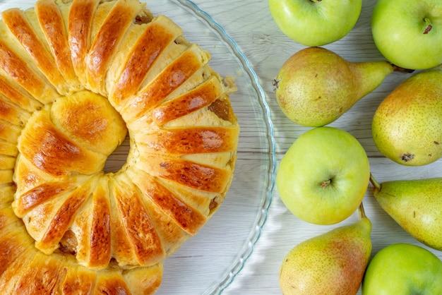 Von oben gesehen gebackener köstlicher gebäckarmreif gebildet innerhalb der glasplatte zusammen mit äpfeln und birnen auf weißem, gebäckkeks süßem auflauf