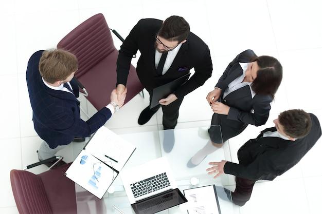 Von oben gesehen. handschlag der finanzpartner beim treffen im büro