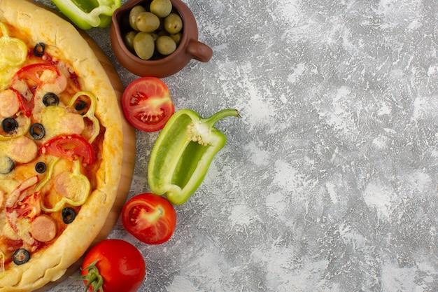 Von oben gesehen köstliche käsige pizza mit olivenwürsten und tomaten auf dem grauen schreibtisch fast-food-italienisches teigmehl