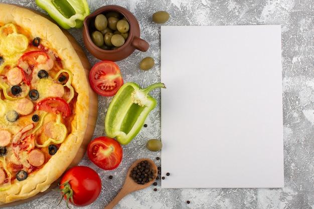 Von oben gesehen köstliche käsige pizza mit olivenwürsten und tomaten auf dem grauen schreibtisch mit papierleer-fast-food-italienischem teigmehl