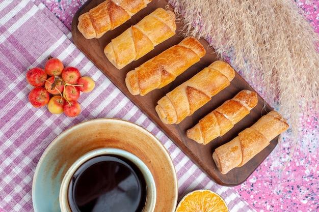 Von oben gesehen köstliche kleine bagels mit tasse tee und zitrone auf hellrosa schreibtisch.