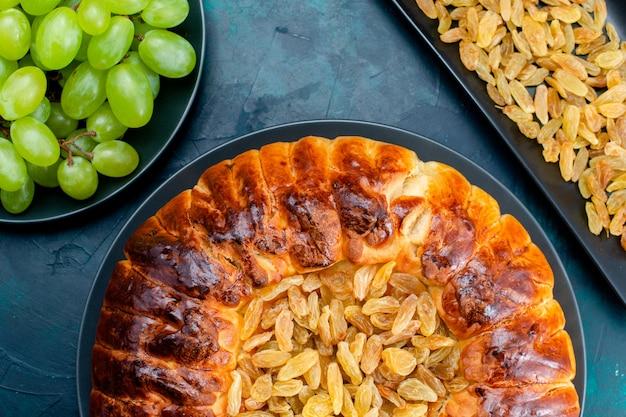 Von oben gesehen köstlicher gebackener kuchen mit erhöhungen und frischen grünen trauben auf dunkelblauem wandkuchenkuchenzuckersüßkeksteig