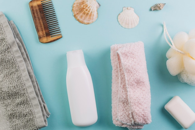 Von oben handtücher und rechen in der nähe der kosmetikflasche