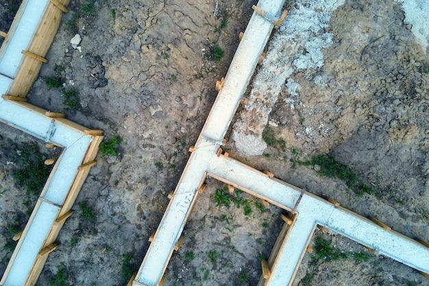Von oben nach unten luftaufnahme der bauarbeiten des neuen hausbetonfundaments auf der baustelle.