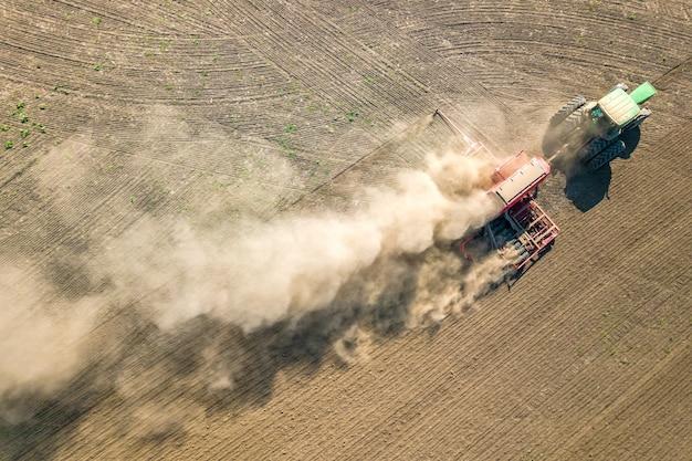 Von oben nach unten luftaufnahme des grünen traktors, der boden kultiviert und ein trockenes feld aussät