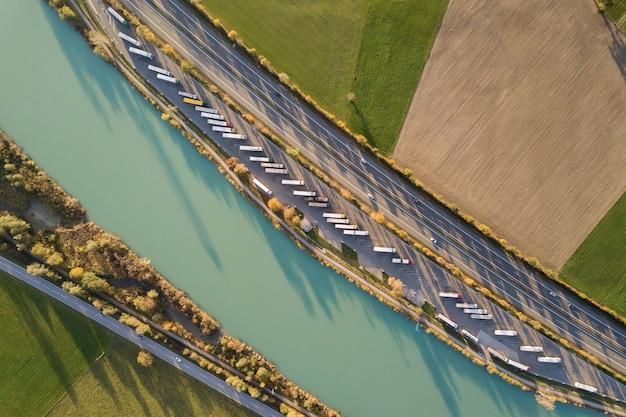 Von oben nach unten vogelperspektive der autobahn mit schnellem verkehr und parkplatz mit geparkten lastwagen.
