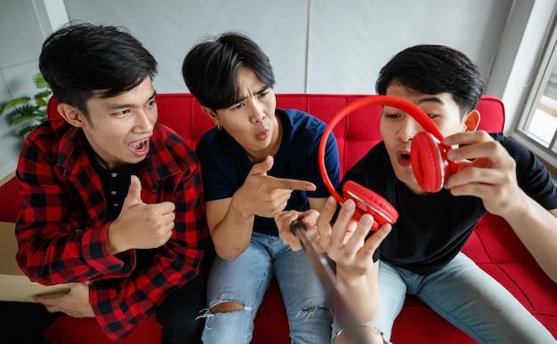 Von oben schockierte asiatische männliche freunde, die eine rezension zeitgenössischer kopfhörer für den technologie-vlog aufnehmen, während sie zu hause auf dem sofa sitzen