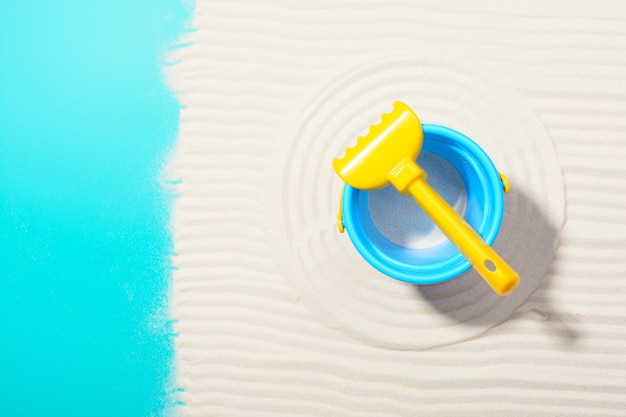 Von oben schuss von blauem eimer und gelbem rechen auf strukturiertem sand