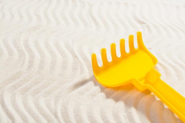 Von oben schuss von gelbem plastikrechen für sandkasten und zeichnen auf sand.