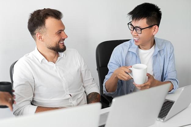 Von oben verschiedene männer lächeln und schauen sich an, während sie mit laptops am tisch sitzen und während der büropause miteinander kommunizieren