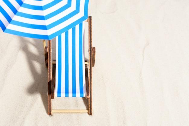 Von oben vom loungebereich am strand mit gestreiftem stuhl unter sonnenschirm.