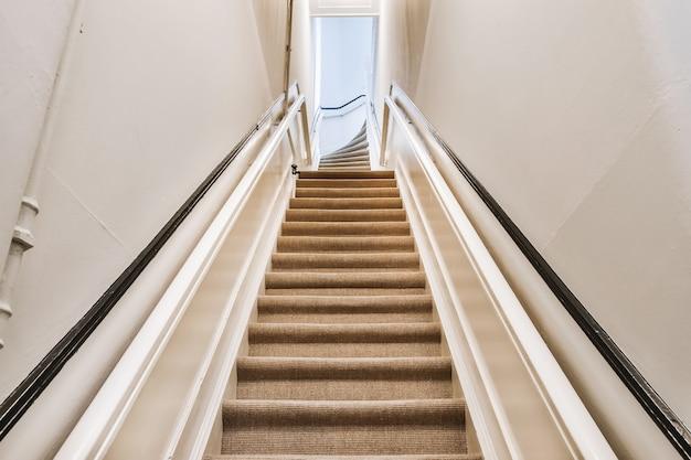 Von unten perspektivische ansicht der treppe zum obergeschoss mit handläufen und teppich auf stufen