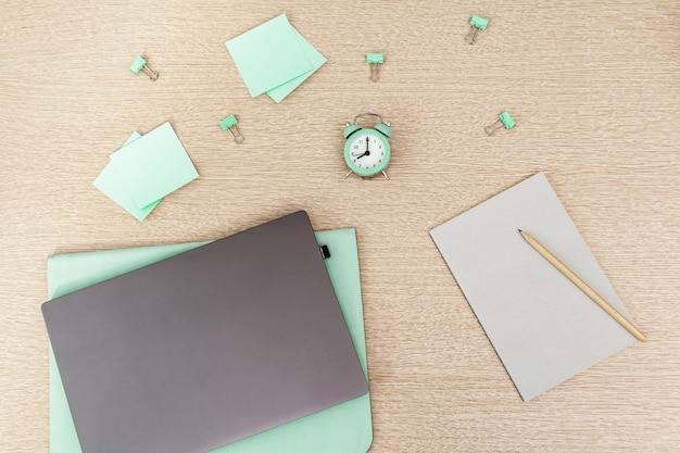 Von zu hause aus arbeiten. laptop für die arbeit und uhr für die tägliche kontrollzeit, notizpapier zum schreiben. arbeitsbereich für freiberufler. draufsicht.