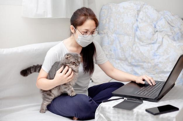 Von zu hause aus arbeiten, studieren, kreativer raum, konzept. freiberufler der asiatischen geschäftsfrau mit hilfskatze, die an laptops und computern zu hause arbeitet. menschen zu hause in quarantäne zu virus outbreak covid-19