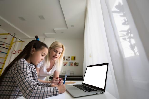 Von zu hause aus mit kind arbeiten. glückliche tochter, die mutter umarmt. junge frau und süßes kind mit laptop. freiberuflicher arbeitsplatz. frauengeschäft, fernunterricht. lebensstil familie moment.