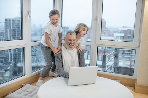 Von zuhause aus arbeiten. grauhaariger bärtiger mann, der am laptop arbeitet, während seine kinder ihn stören