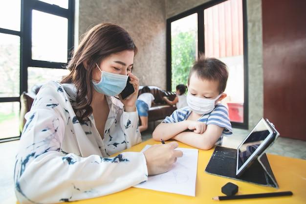Von zuhause aus arbeiten. mutter telefoniert und spielt mit ihrem sohn, während sie sich für coronavirus covid-19 unter quarantäne stellt. mutter und sohn tragen eine schutzmaske, während sie zu hause während des ausbruchs des coronavirus arbeiten.