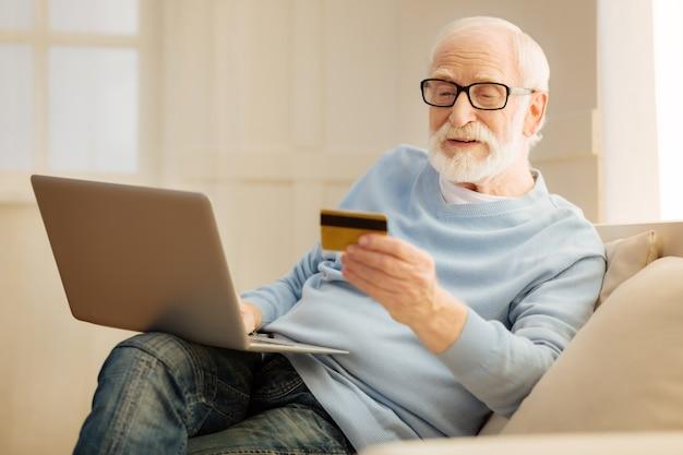 Von zuhause aus einkaufen. art lächelnder männlicher faltiger stirn und haltekarte beim online-einkauf