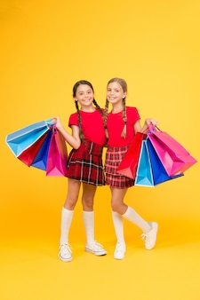 Von zuhause aus einkaufen. große verkäufe. schulmädchen mit paketen. kaufen. schwarzer freitag. urlaub präsentiert. verkauf und rabatt. mädchen einkaufen. glückliche kinder mit einkaufstüten. erfolgreich einkaufen.