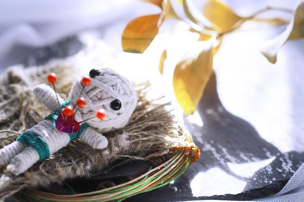 Voodoo-puppe auf steinhintergrund mit dramatischer beleuchtung. mystisches stillleben mit voodoo-puppe, den tarotkarten, büchern, bösen kerzen und hexerei-objekten. wahrsagerei ritus.