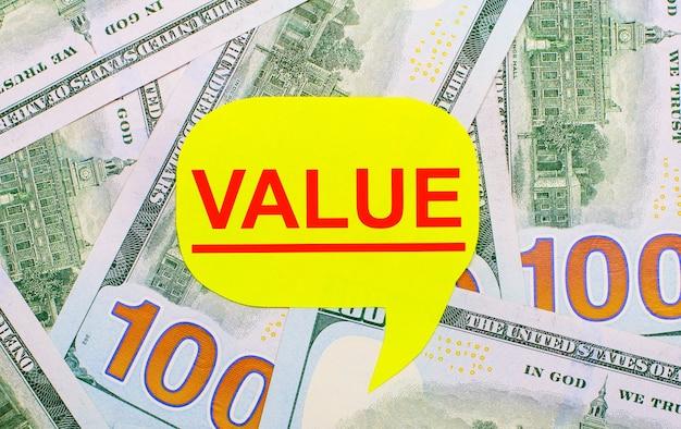 Vor dem hintergrund der auf dem tisch verstreuten dollars befindet sich eine gelbe, geschweifte karte mit dem text wert. finanzkonzept