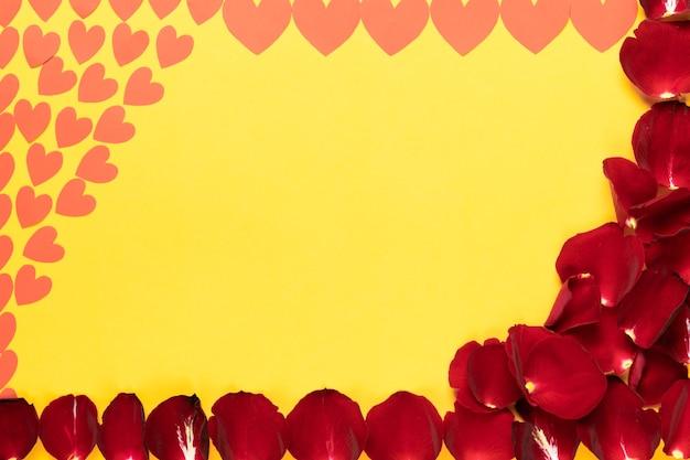 Vor dem hintergrund der inschrift liegen rote rosenblätter und papierherzen in verschiedenen größen