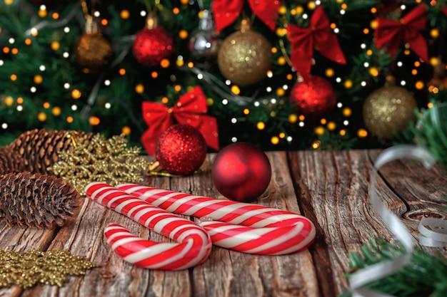 Vor dem hintergrund der weihnachtsfichte karamellstäbe mit weihnachtskugeln und fichtenzapfen