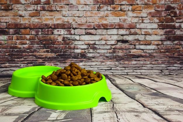 Vor dem hintergrund grauer holzbretter liegt ein grüner plastikteller gefüllt mit trockenfutter zur fütterung von katzen oder hunden. rechts ist platz für eine inschrift oder werbung