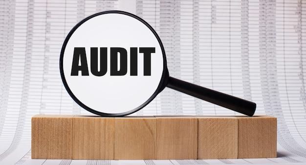 Vor dem hintergrund von berichten über holzwürfel - eine lupe mit dem text audit. geschäftskonzept