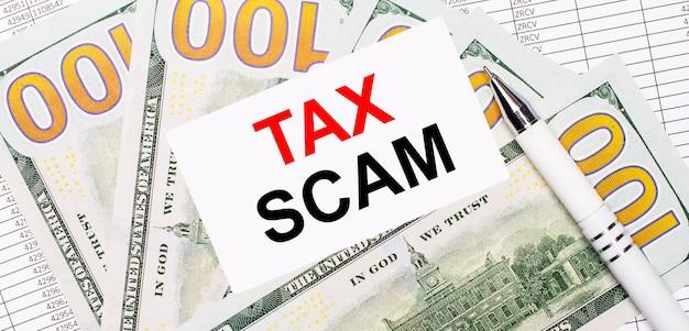 Vor dem hintergrund von berichten und dollars - ein weißer stift und eine karte mit dem text tax scam. geschäftskonzept