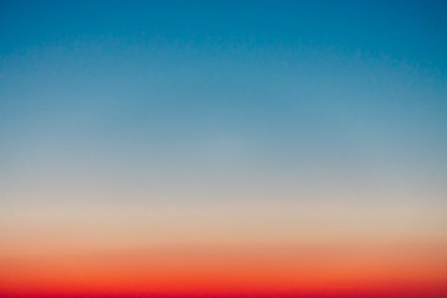 Vor dem morgengrauen klarer himmel mit rotem horizont und blauer atmosphäre. glatter orange-blauer farbverlauf des morgenhimmels. hintergrund des tagesanfangs. himmel am frühen morgen mit kopierraum.