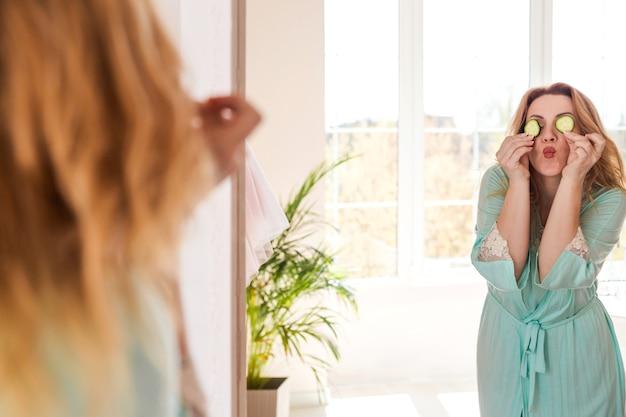 Vor dem spiegel steht eine schöne frau mit bademantel und gurkenscheiben vor den augen