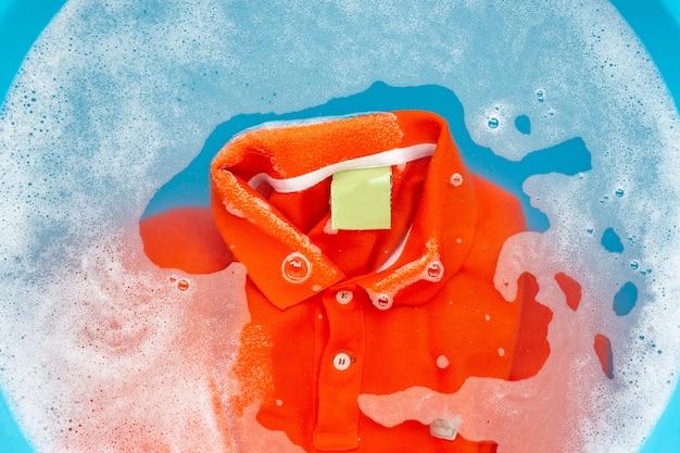 Vor dem waschen ein tuch einweichen, orangefarbenes poloshirt. ansicht von oben