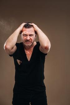 Vor einem grauen hintergrund steht ein ramponierter wütender mann in einem schwarzen t-shirt