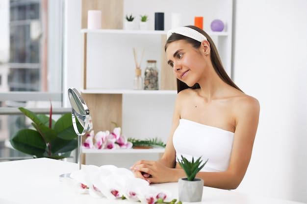 Vor einem spiegel stehen und schönheitsbehandlungen für sich genießen