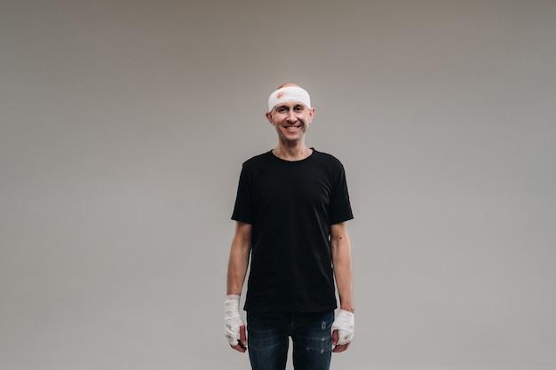 Vor grauem hintergrund steht ein angeschlagener und angeschlagener mann in einem schwarzen t-shirt, den kopf in einen verband gewickelt.