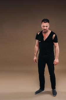 Vor grauem hintergrund steht ein angeschlagener wütender mann in einem schwarzen t-shirt mit wunden