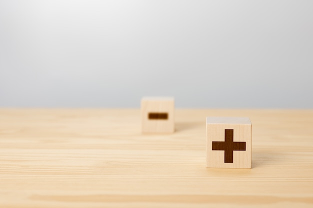 Vor- und nachteile konzept wählen sie plus mit verschwommenem minus-symbolkonzept von gegensätzen holzblock