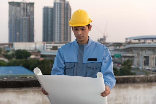 Vorarbeiter blick auf blaupause auf einer baustelle