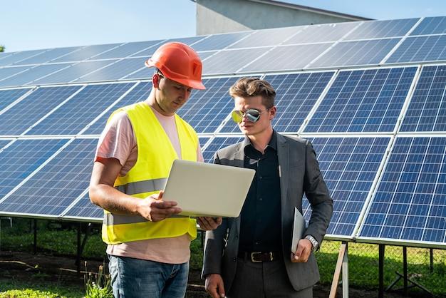 Vorarbeiter, der photovoltaik-detailgeschäftsmann an der solarenergiestation zeigt. grüne energie