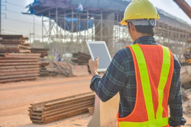 Vorarbeiter, der tablette hält, verwenden technologie-inspektionssteuerungsbaustelle