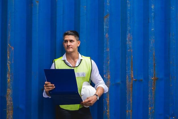 Vorarbeiter hält dokument, geht und überprüft die containerbox vom frachtschiff für den export und import