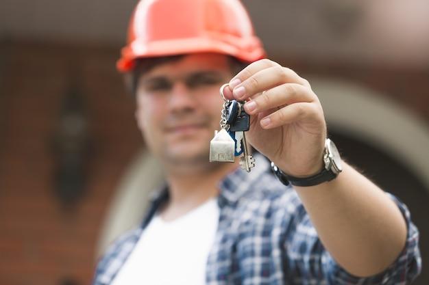 Vorarbeiter im bauarbeiterhelm, der schlüssel des neuen hauses gibt
