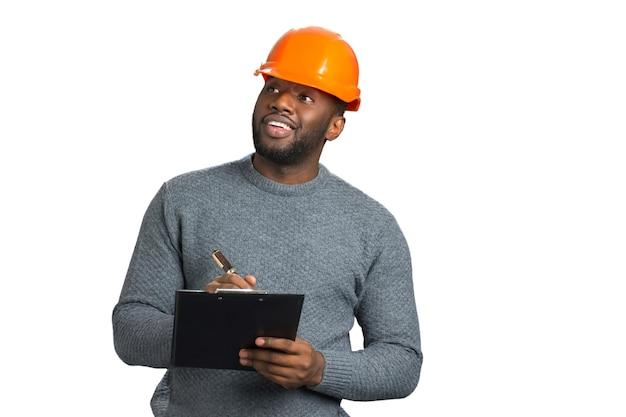 Vorarbeiter im freizeitbekleidungsprüfobjekt. positiver junger architekt, der das bauen und schreiben betrachtet