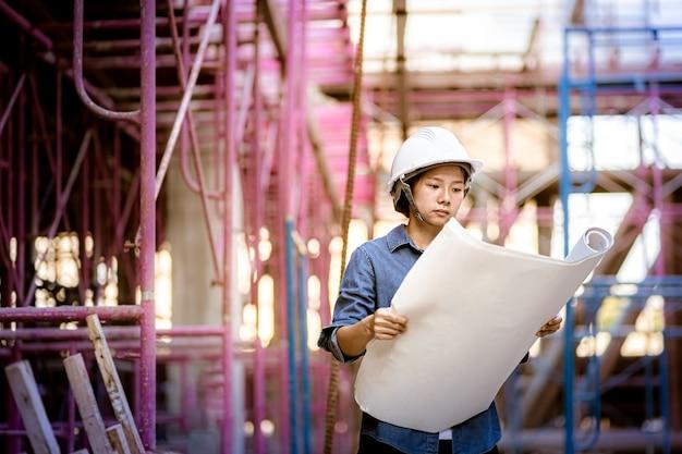 Vorarbeiterin inspiziert baustelle. technische frau, die blaupause hält zeichnungslayout hält. frau, die schutzhelm trägt.