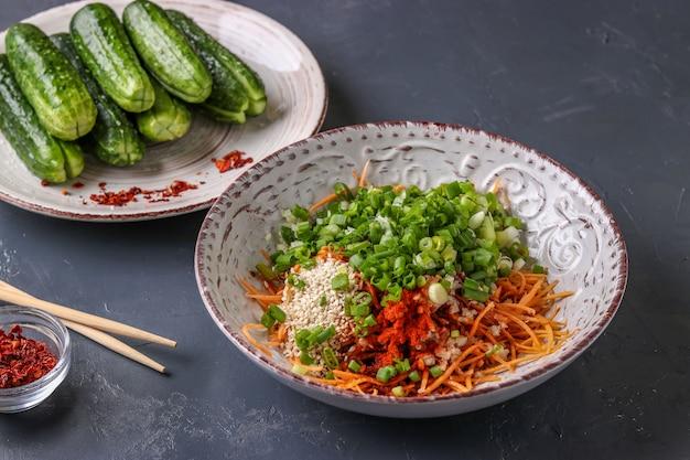 Vorbereiten der produkte für das kochen des traditionellen koreanischen gurkenkimchisnacks: mischen von bestandteilen in einer schüssel, fermentiertes lebensmittel