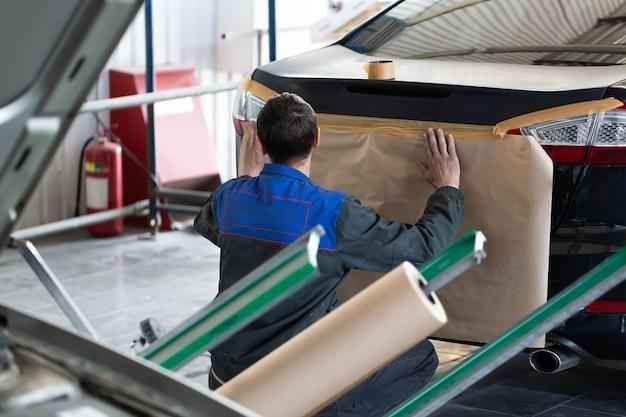 Vorbereiten des autos und der autostoßstange für das lackieren auf karosseriewerkstatt