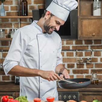 Vorbereiten des lebensmittels des männlichen chefs in der bratpfanne