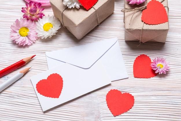 Vorbereiten des valentinstagsgeschenks, der geschenkboxen und des umschlags auf hölzernem hintergrund