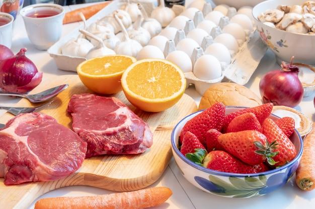 Vorbereiten für das kochen am abendessen mit rindfleisch, obst, gemüse und aromen auf tisch